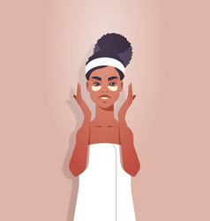 Young woman applying eye patches dressed in towel vector
