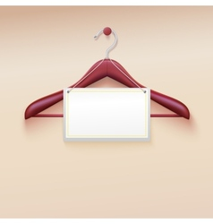 Clothes hanger with tag isolated on cream vector