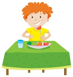 Little boy eating on the table vector