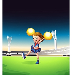 A pretty young cheerleader at the field vector image