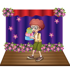 A stage with a young boy holding gifts vector image vector image