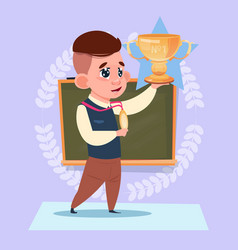 small school boy hold winner cup standing over vector image