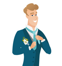 young caucasian cheerful groom adjusting tie vector image