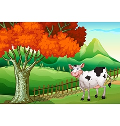 A smiling cow near the big tree vector image