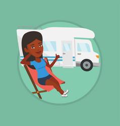 Woman sitting in chair in front of camper van vector