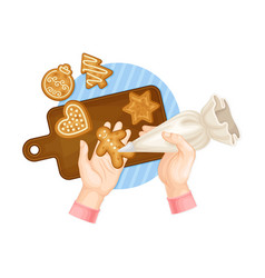 Hands decorating gingerbread cookie with sugar vector