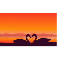 silhouette of two swan at sunset scenery vector image
