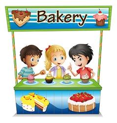 Three kids in a bakery stand with cupcakes vector