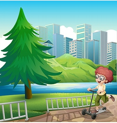 A happy young boy playing with his scooter near vector image