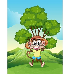A playful monkey at the hilltop near the tree vector image