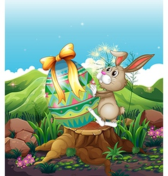 A bunny and a big Easter egg above the stump vector image