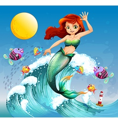 A big wave with a mermaid and a school of fishes vector