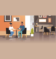 Young couple drinking coffee together sitting cafe vector