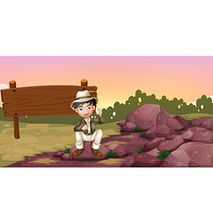 A boy sitting on a rock near an empty signboard vector image