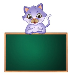 A cat leaning above the empty blackboard vector image