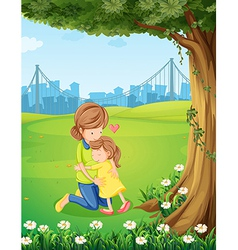 A mother hugging her daughter under the tree vector image vector image