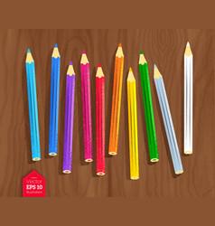Color pencils on wooden desk background vector