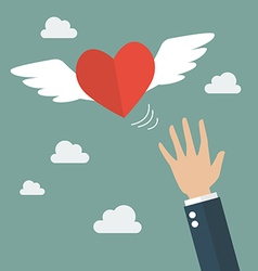Hand catching a heart flying vector image