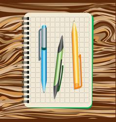 notebook blue pen green pen and yellow pen vector image