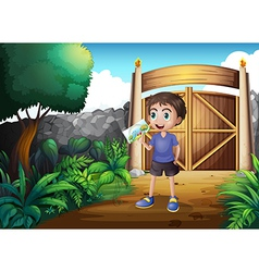 A boy holding picture inside the gate vector