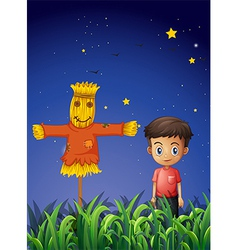 A little boy standing beside the scarecrow vector