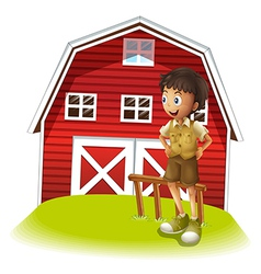 A boy standing in front of the red barnhouse vector