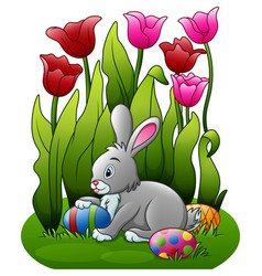 Easter bunny with eggs in the flower garden vector