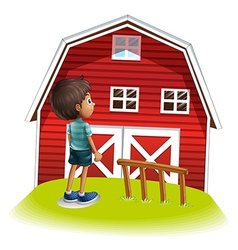 A boy standing in front of the red farmhouse vector image