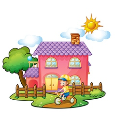 A little boy playing in front of their house vector image