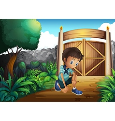 A boy watching ground inside gate vector