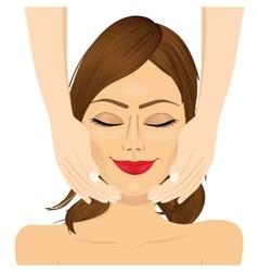 Attractive young woman enjoying facial massage vector