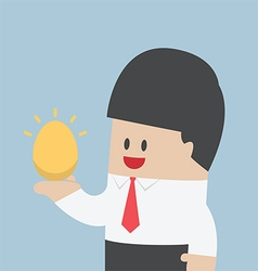 Businessman holding golden egg in his hand vector image