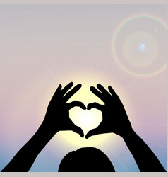 hand silhouettes forming a heart with sun inside vector image