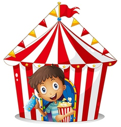 A young boy with a ticket and a popcorn near the vector image