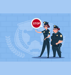 two police women holding stop sign wearing uniform vector image