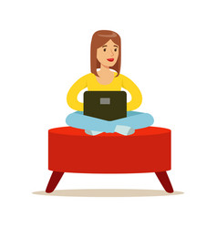 Happy young woman sitting in a red pouf and using vector