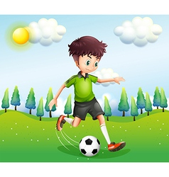 A boy playing football in the hill vector image vector image