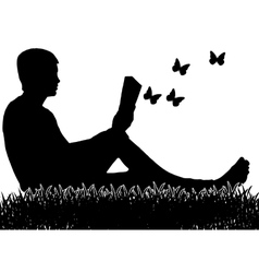 The man who is sitting on the grass and reading a vector