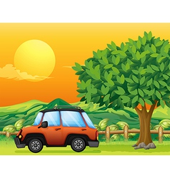 An orange vehicle near the big tree vector