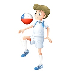 A boy using the ball with the Chile flag vector