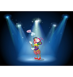 A clown performing on a stage under the spotlights vector image