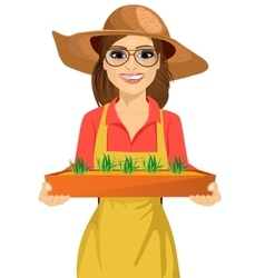 Young farmer woman holding box of seedlings plants vector image