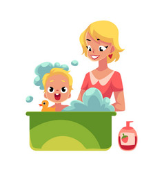 young mother washing her baby in bathtub full of vector image