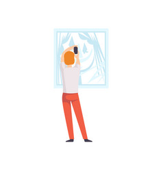 Man photographing a picture hanging on the wall vector