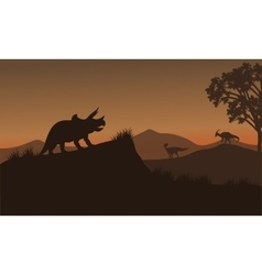 Triceratops and Eoraptor silhouette in hills vector