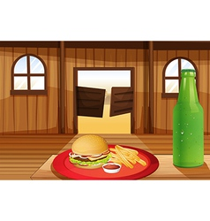 A burger and fries in a red plate and a bottle of vector image