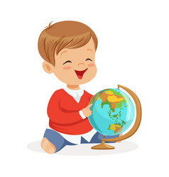 Smiling little boy sitting and playing with globe vector