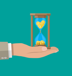 old hourglass clocks with coins inside in hand vector image vector image
