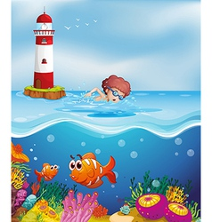 A boy swimming with fishes and corals at the beach vector image vector image