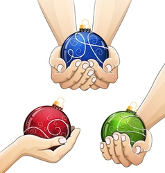 Hands holding Christmas balls vector
